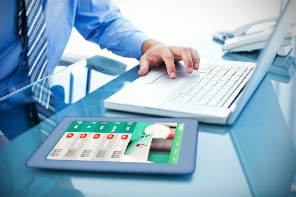 case de pariuri recomandate barbatul utilizeaza laptopul si tableta in oficiu