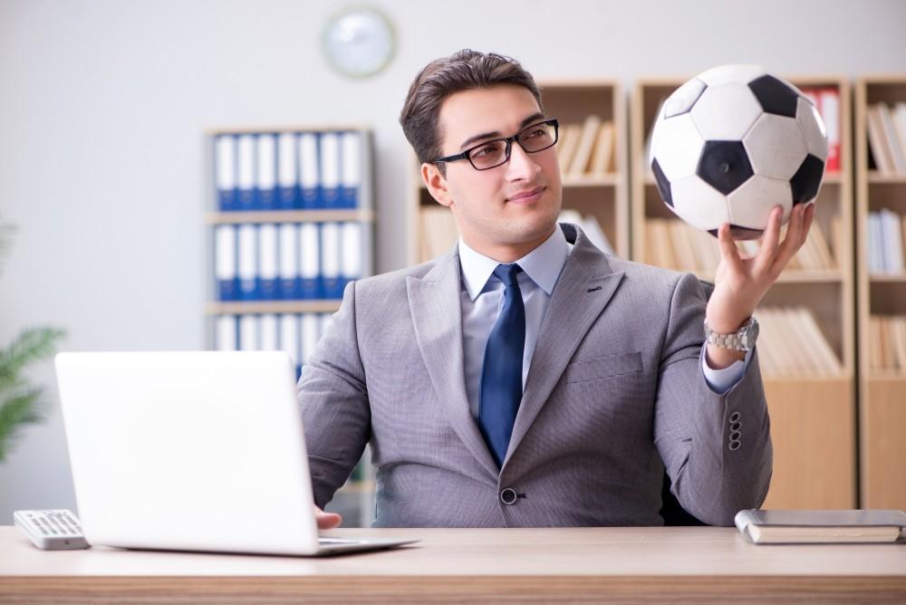 case de pariuri recomandate barbat in oficiu cu o minge si laptop in maini
